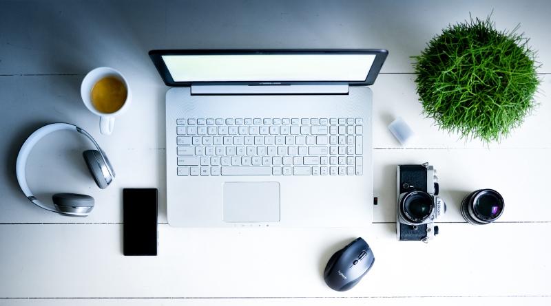 biały laptop na biurku ze słuchawkami, kawą, myszką
