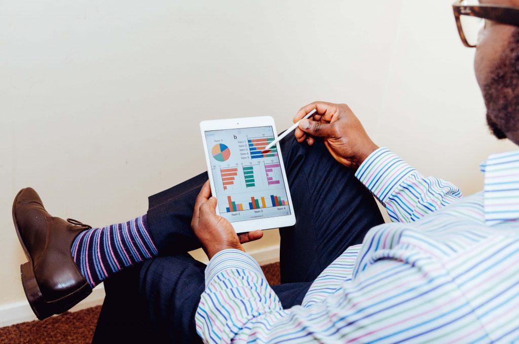mężczyzna oglądający wykresy na tablecie