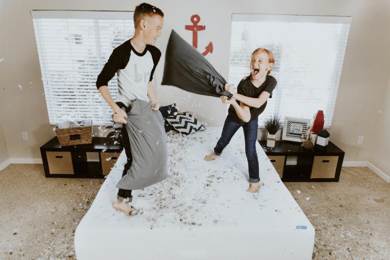 Dwoje dzieci bawiących się na łóżku