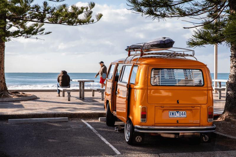 Bus stojący na parkingu, a w tle morze