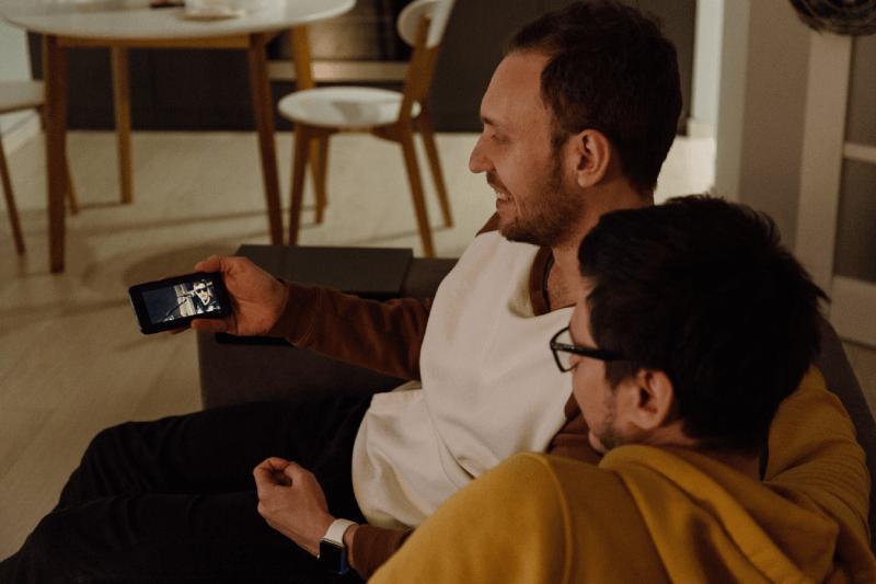 Dwóch mężczyzn oglądających filmik na domówce
