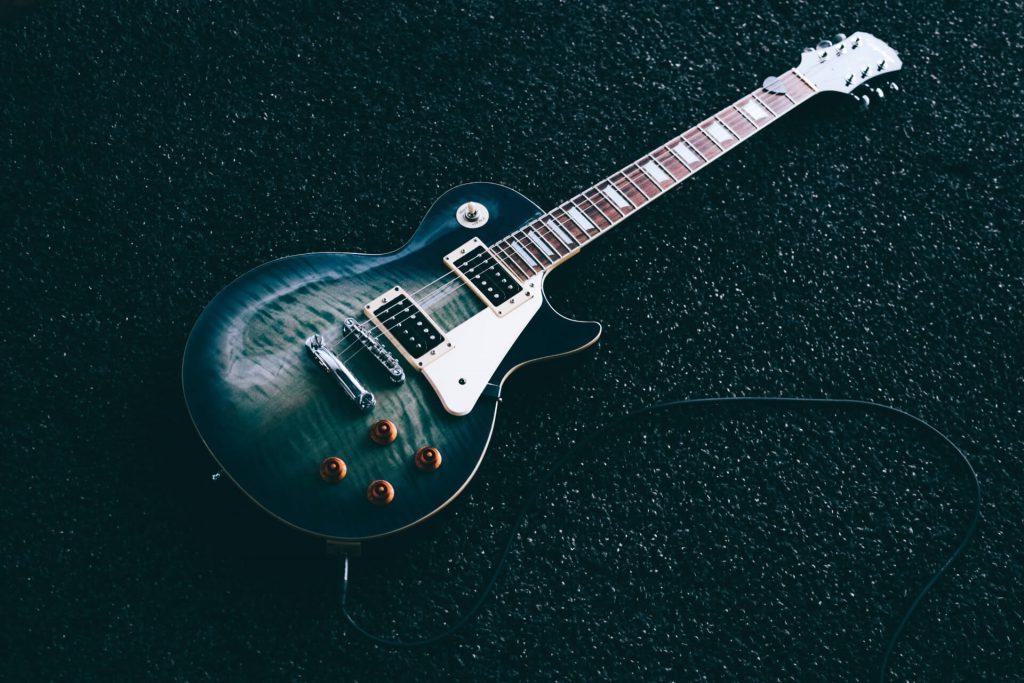 Czarna gitara elektryczna podłączona do wzmacniacza