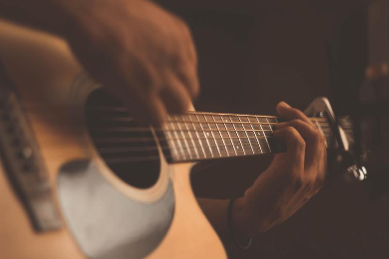Osoba grająca na gitarze