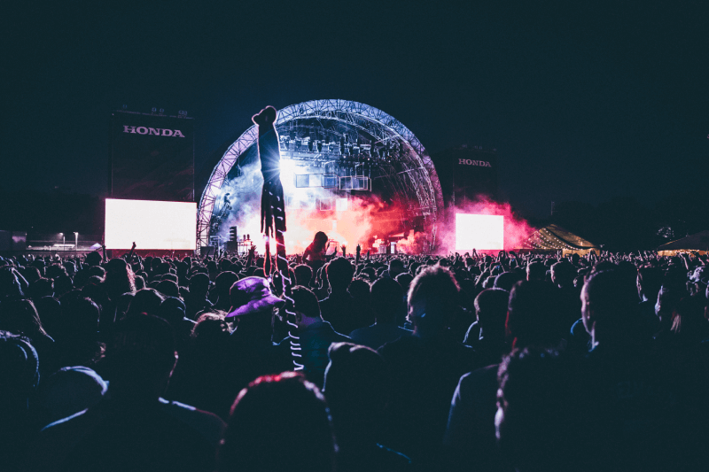 Ludzie bawiący się na koncercie w plenerze