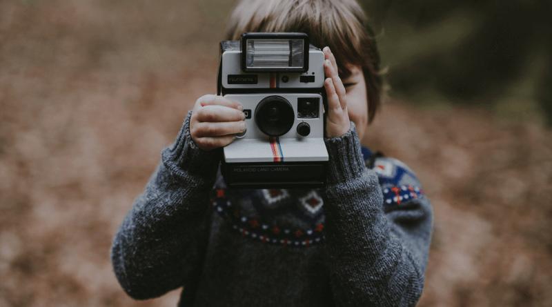 Dziecko robiące zdjęcie aparatem polaroid